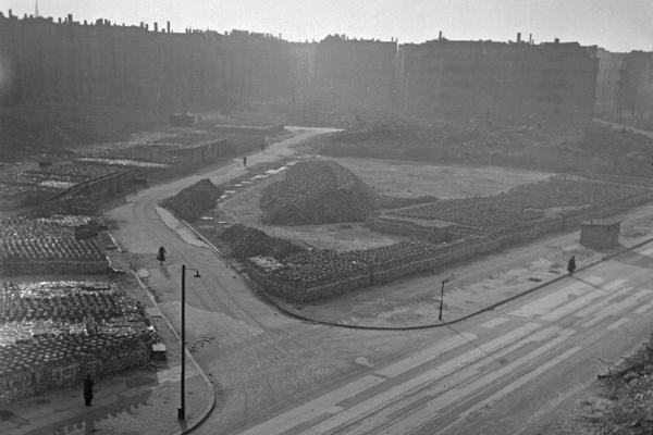 Undatierte Aufnahme eines Straßenzugs in Berlin, vermutlich Westberlin, 1950 mit enttrümmerten Brachflächen. Links der Straße sind Ziegel zum Bau von neuen Häusern aufgestapelt. Im Vordergrund sind Straßenschilder, Laternen und eine mit Plakaten bekelebte Litfaßsäule zu sehen. Am Horizont sind teilweise zerstörte Wohnblöcke zu sehen.