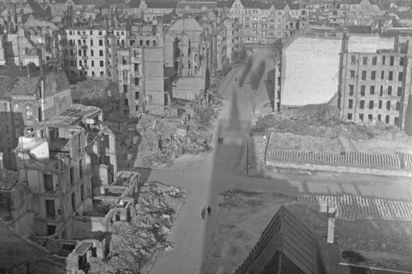 Undatierte Aufnahme eines teilweise zerstörten fast menschenleeren Straßenzugs in Berlin, vermutlich Westberlin, 1950. Links und rechts der Straße sind teilweise zerstörte Häuser sowie Häusergerippe zu sehen. Rechts der Straße wurde mit der Enttrümmerung begonnen. Zu sehen sind Ziegelstapel für den Wiederaufbau. Im Hintergrund: unzerstörte Häuser. Am Horizont im Nebel liegt der zerstörte Turm der Kaiser-Wilhelm-Gedächtniskirche.