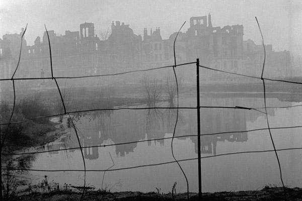Undatierte Aufnahme einer im Nebel liegenden durch alliierte Bombardements zerstörten Häuserzeile vermutlich in Westberlin 1950. Das Foto wurde durch einen Drahtzaun gemacht. Im Vordergrund ist ein mit Regenwasser gefüllter Bombentrichterr zu sehen.
