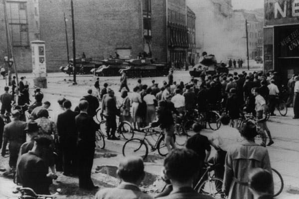 Aufstand des 17. Juni in der DDR. Im Vordergrund Demonstranten mit Fahrrädern und im Hintergrund vorrückende sowjetische Panzer.