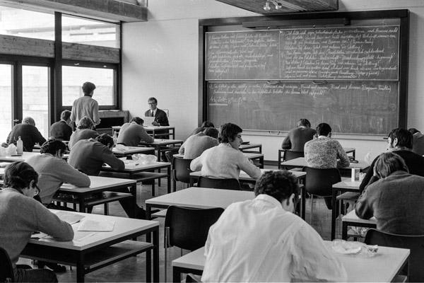 Der Lehrer ist erstaunt! Der erste Schüler gibt seine Arbeit ab.