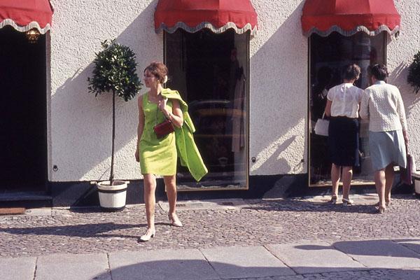 Frau in einem grünen Kleid vor einer Boutique am Kurfürstendamm in Berlin.