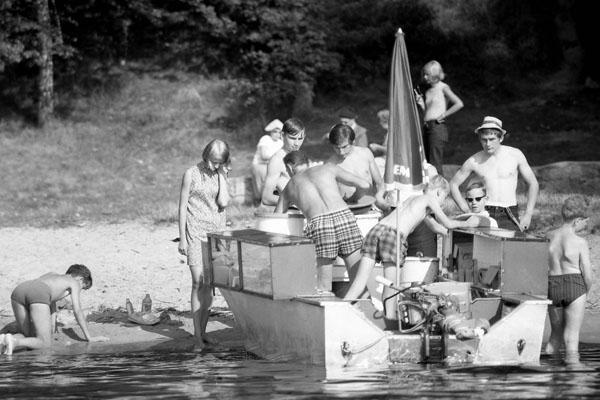 Badestelle an der Havel in Berlin. Bild zeigt ein Motorboot als Verkaufsstand und Jungen in Badehose.