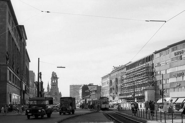 KaDeWe (links) in der Tauentzienstraße in Berlin, im Hintergrund die Kaiser Wilhelm Gedächtnis Kirche und im Vordergrund eine Straßenbahn, Autos und Passanten.
