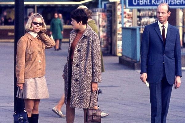 Frauen mit Rock, Mantel, Sonnenbrille und Handtasche und ein Mann im Anzug an der U-Bahn Haltestelle Kurfürstendamm in Berlin.