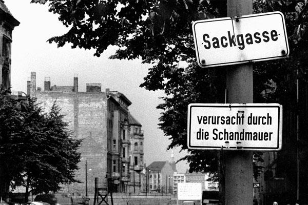 """Ein Schild mit der Aufschrift """"Sackgasse"""" und einem weiteren, von Aktivisten angebrachten Schild mit der Aufschrift """"verursacht durch die Schandmauer"""" vor einer Straße, die plötzlich an der Berliner Mauer der DDR endet."""