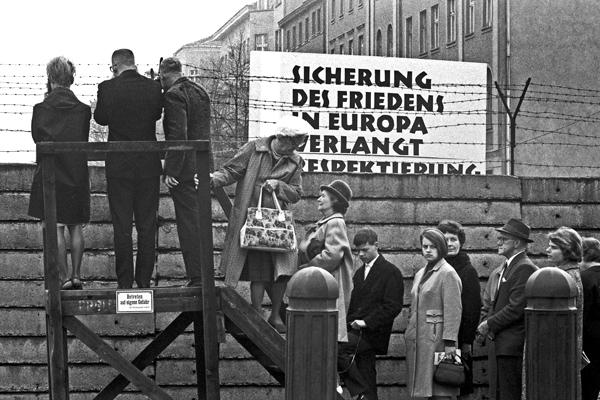 Menschen stehen auf und vor einem Podest in an der Mauer in Berlin, um einen Blick über den Grenzzaun werfen oder mit Betroffenen Sichtkontakt aufnehmen zu können.