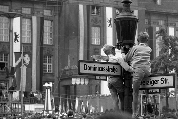 Zwei Jungen klettern auf Straßenschilder, um die Kungebung und die Demonstration zum ersten Jahrestag des Mauerbaus vor dem Schöneberger Rathaus in Berlin zu verfolgen.