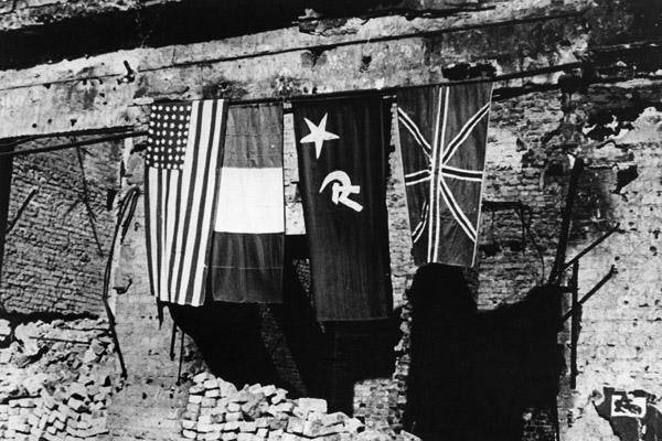 Die vier Nationalflaggen der Besatzungsmächte /  Deutschlands hängen über einem Trümmerhaufen.  Militärregierung der Besatzungsmächte, Nachkriegszeit, Deutschland 1945-1949, Westdeutschland