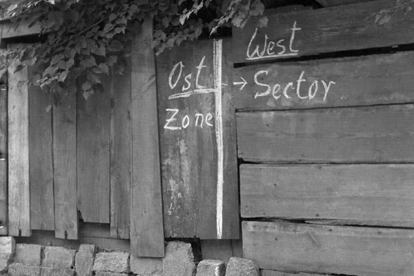 Aufnahme einer einer Kreidemarkierung der Zonengrenze zwischen dem West-Sektor und der Ost-Zone 1950 in Berlin. Am Boden wird die Linie durch einen Strich im Sand weitergeführt. Das Foto wurde nach der Währungsreform 1948 in einem Ausflugslokals, das unmittelbar auf der Zonengrenze zwischen Ost- und Westberlin liegt, gemacht.