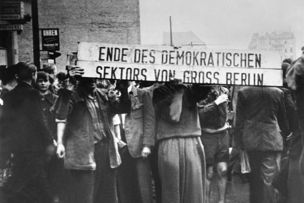 """Demonstrierende Arbeiter halten die Reste eines Sektorenschildes hoch (""""Ende des demokratischen Sektors von Gross Berlin"""")."""