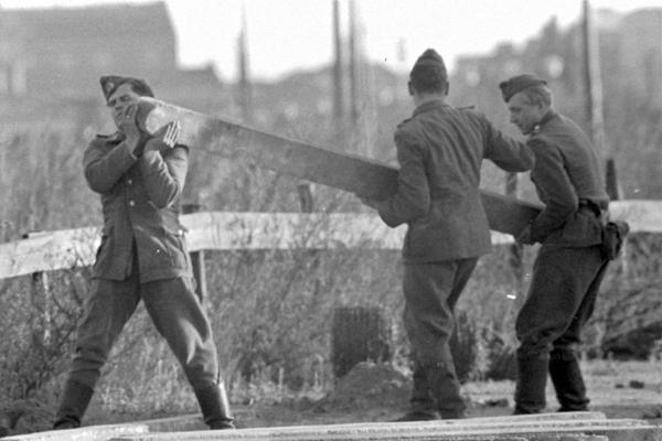 Bau der Berliner Mauer am Potsdamer Platz: NVA-Soldaten tragen einen Pfeiler.