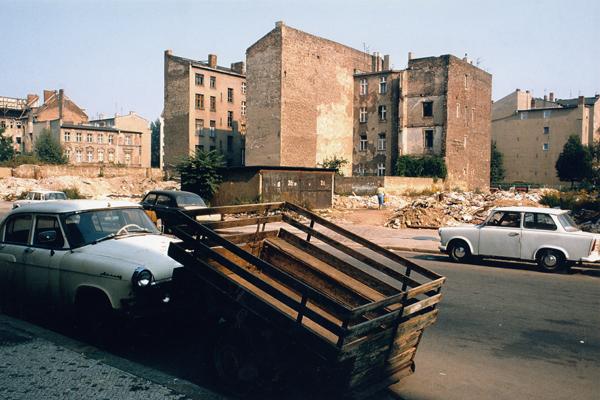 Ein geparktes Auto neben einem Anhänger in einer Straße vor heruntergekommenen Wohnhäusern am Prenzlauer Berg in Berlin.