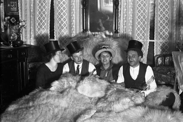 Zwei Damen und zwei Herren feiern Weihnachten leicht angetrunken auf Schaffellen aufe einem Bett.