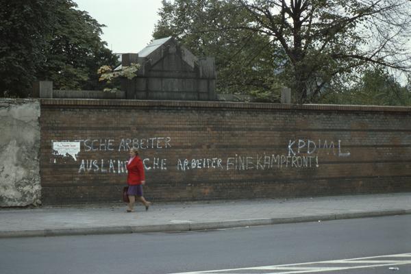 """Politisches Graffito der Kommunistischen Partei Deutschlands / Marxisten-Leninisten an einer Mauer in Berlin: """"DEUTSCHE ARBEITER AUSLÄNDISCHE ARBEITER EINE KAMPFRONT! KPD/ML"""" - teilweise verdeckt von einem Plakat und einer vorübergehenden Frau."""