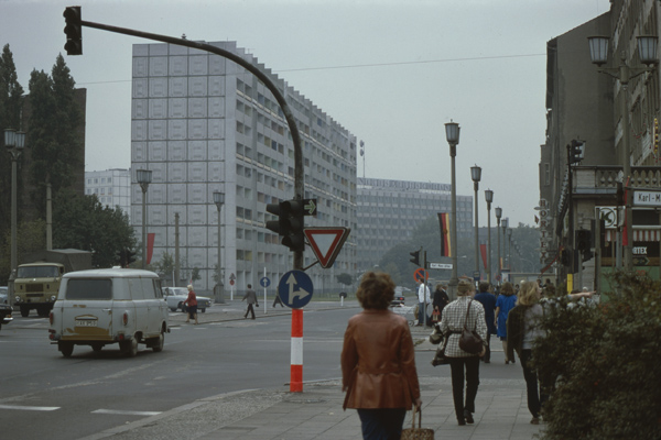 Fußgänger gehen über die mit DDR- und roten (sowjetischen) Flaggen geschmückte Kreuzung Straße der Pariser Kommune / Karl-Marx-Allee - im Hintergrund ist das Verlagsgebäude des Neuen Deutschland zu sehen.