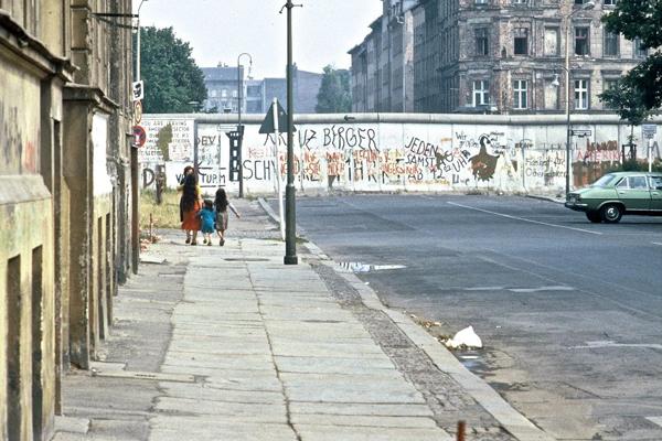 Eine Familie auf dem Bürgersteig vor der mit Graffiti bemalten Mauer in Berlin.