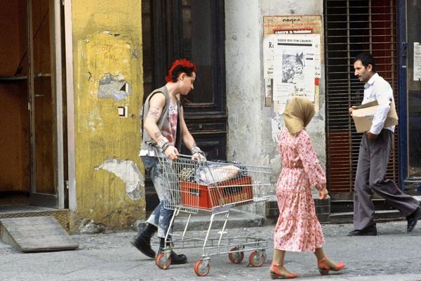 Ein Punk mit rotgefärbten Haaren schiebt einen Einkaufswagen vorbei an einer Frau mit Kopftuch und Kleid in einer Straße in Berlin.
