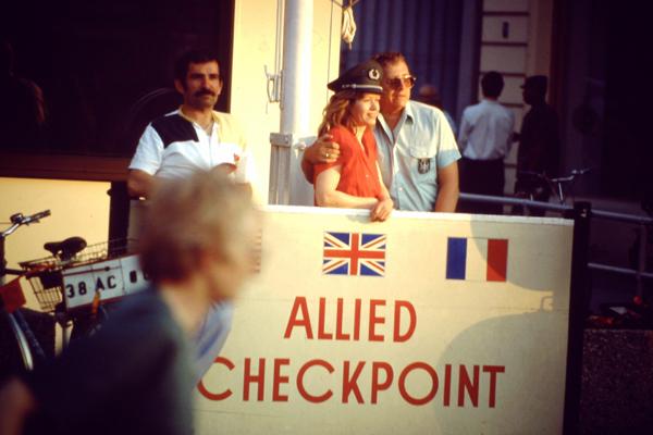 Ein Paar posiert vor dem Allied Checkpoint Charlie, während ein Kind vorbeiläuft.