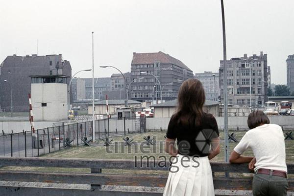 Ein Mann und eine Frau blicken auf die Berliner Mauer in Richtung Ostberlin.