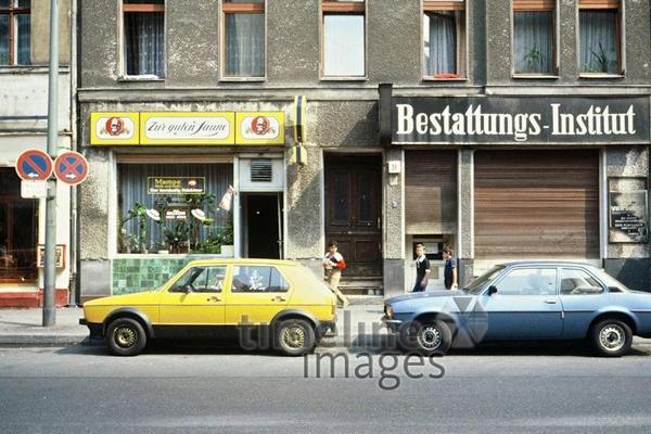Drei Jungen laufen vorbei an geparkten Autos, einem Café und einem geschlossenen Bestattungsgeschäft in Berlin.