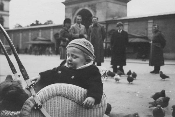 Ein kleiner Junge sitzt in seinem Kinderwagen auf dem Odeonsplatz in München. Im Hintergrund wird er von ein paar älteren Herrschaften beobachtet. Im Hintergrund sieht man den Eingang zum Hofgarten.