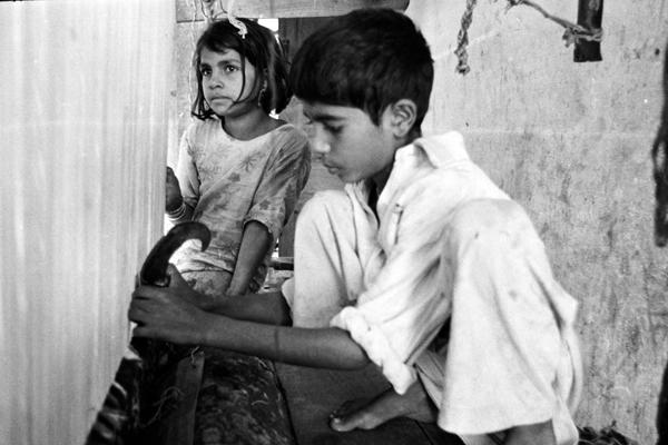 Ein Junge knüpft Teppiche, während seine Schwester ihm zusieht.