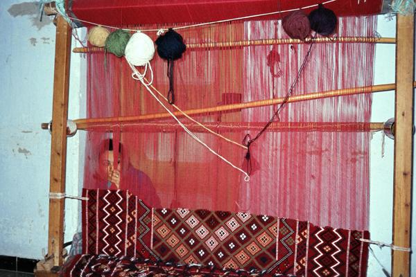 Eine Frau knüpft Teppiche in Kairouan.
